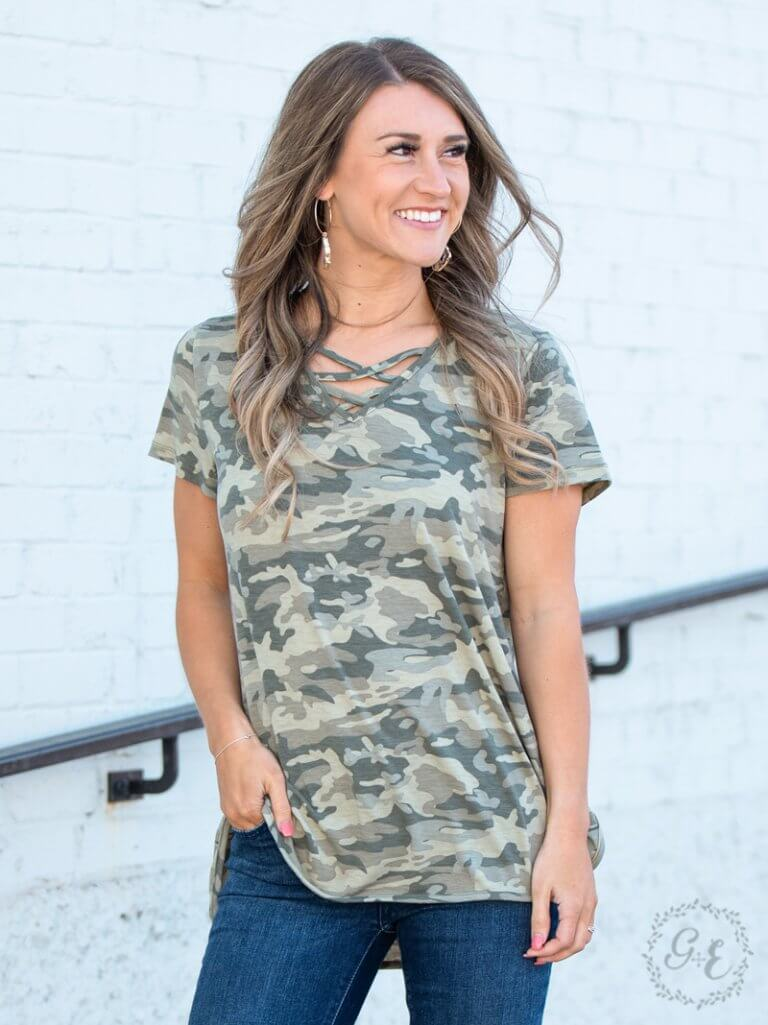 Smiling woman wearing a long, soft-green camo tee shirt with a criss-cross detail at the neck