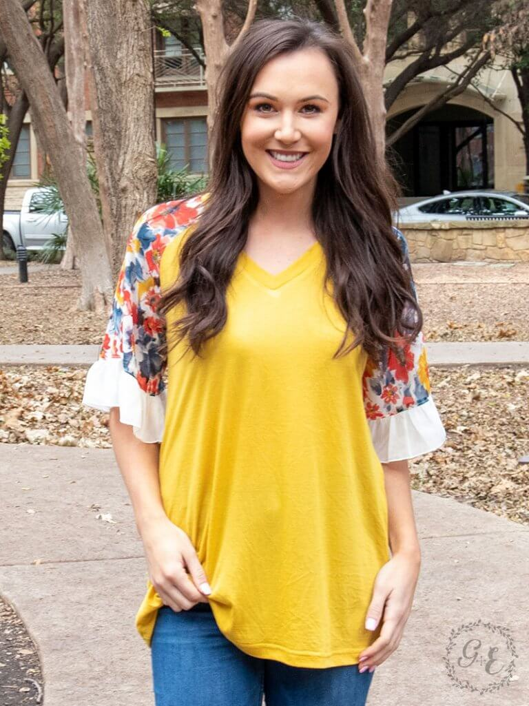 Smiling teenage girl wearing a mustard yellow, flowy shirt with vibrant floral 3/4 in sleeves